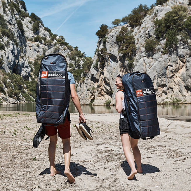 two people walking in a canyon with inflatable sup's on their back