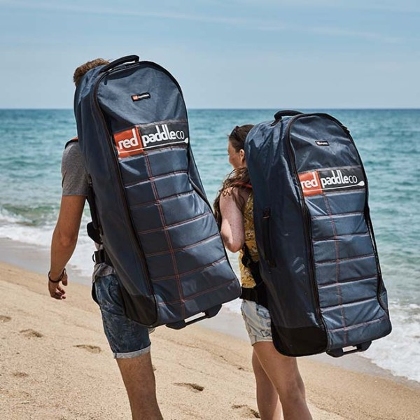 couple walking along beach with inflatable paddle boards in bags on their backs