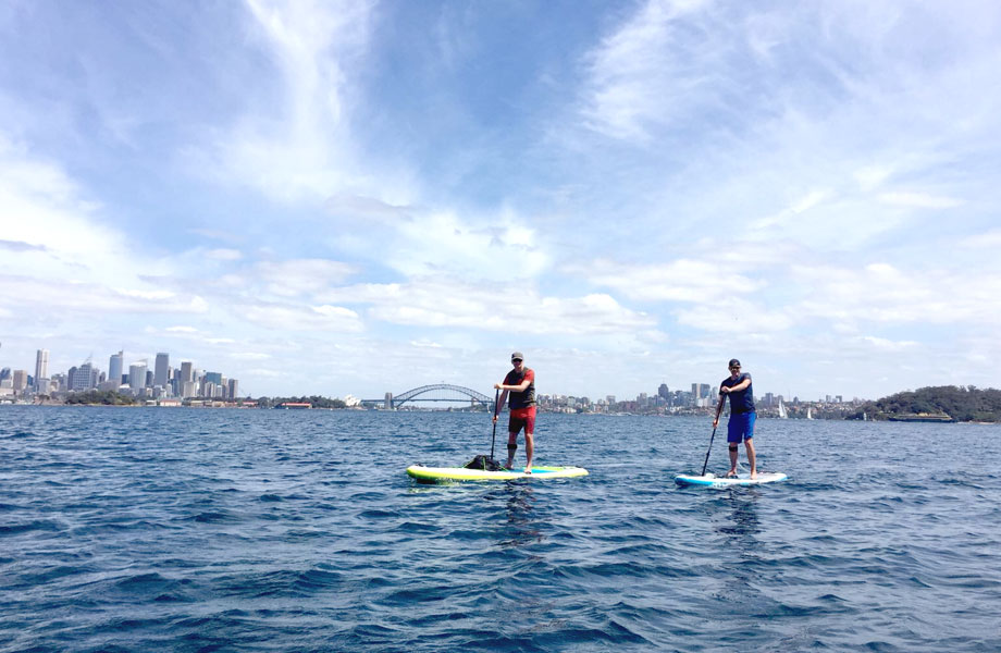 two men on paddle boards in front of Sydney skyline