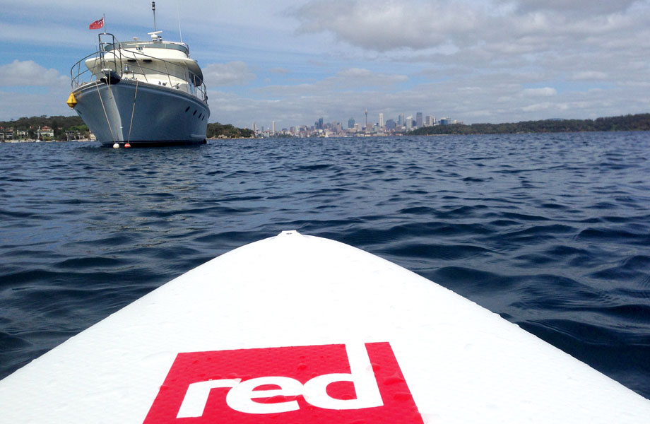 red paddle co board opposite a large boat