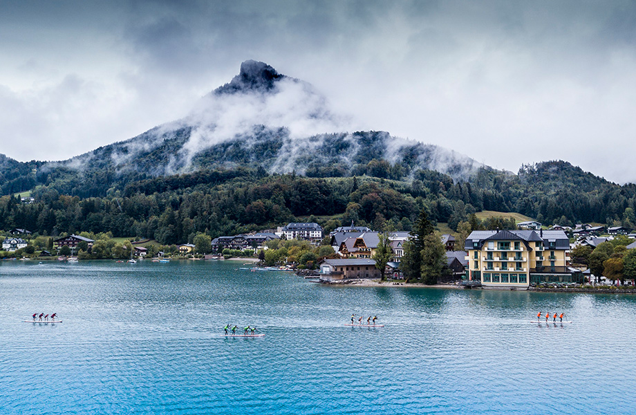 Drone shot the mountains with low hanging misty clouds, four teams of paddlers racing.