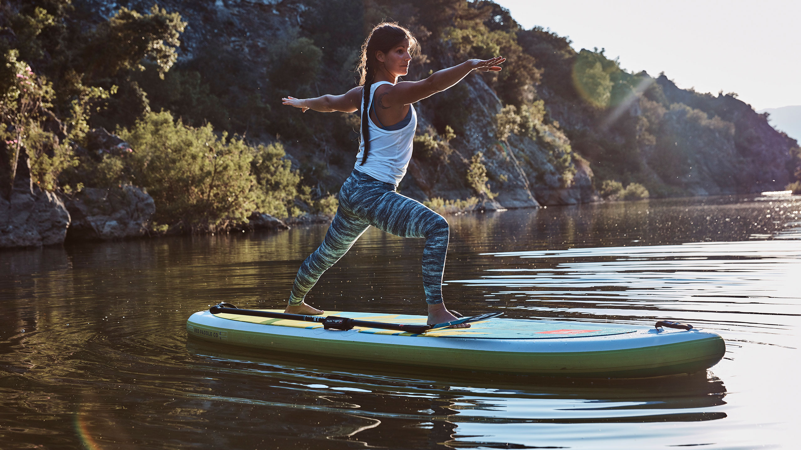 woman stands and holds yoga pose on paddle board