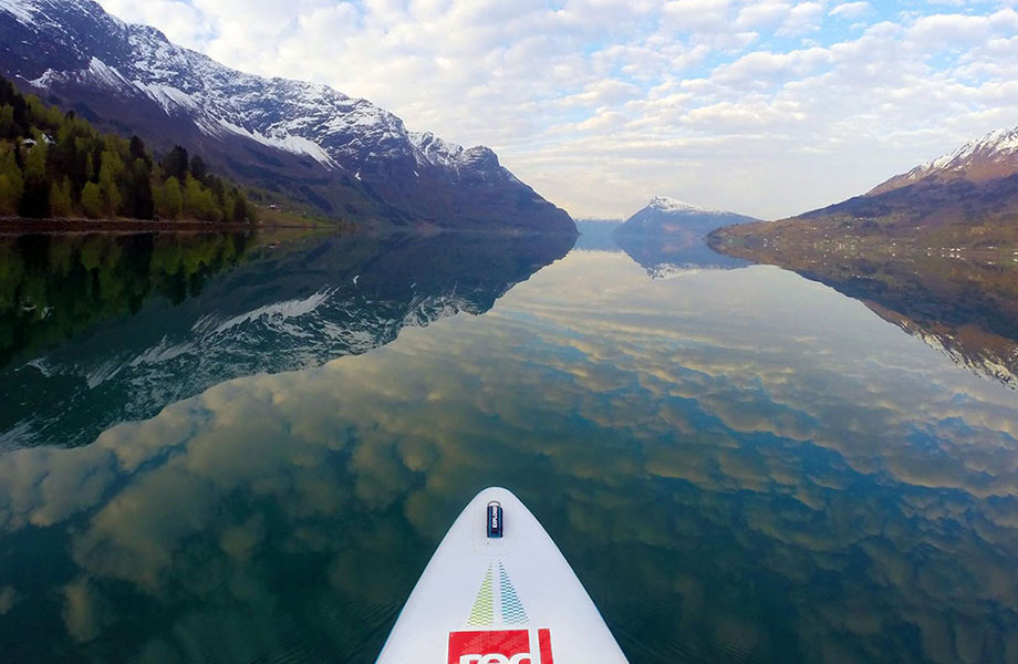 paddle board on glass reflection of Norwegian fjord