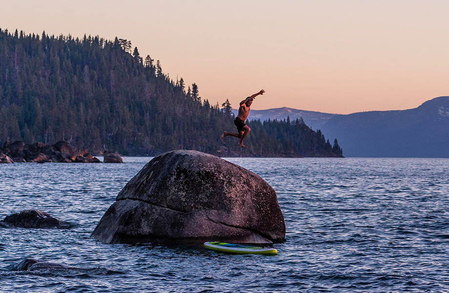 man jumps off rock with SUP on water below
