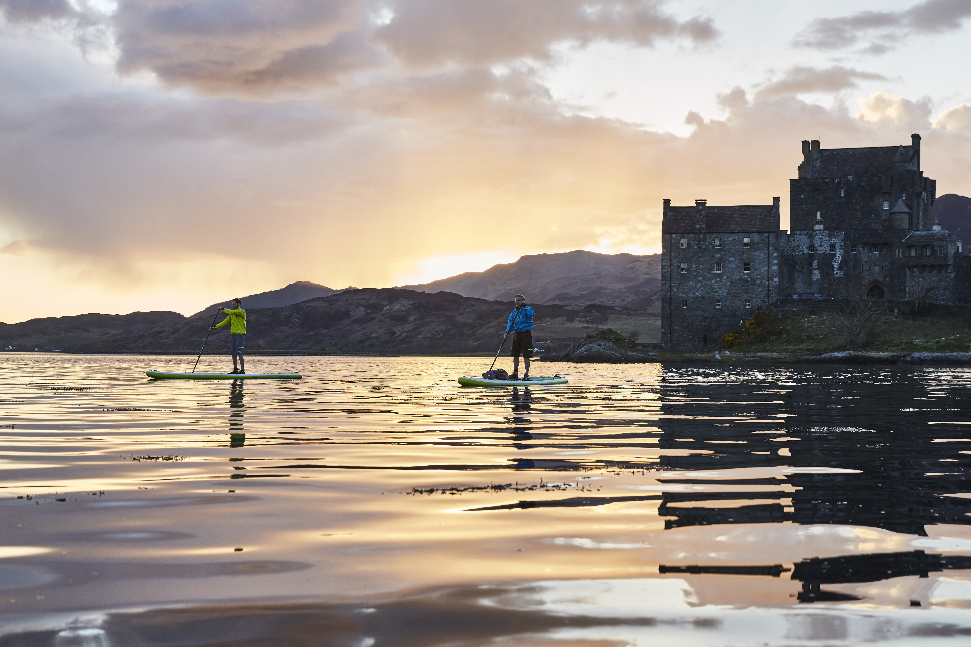 two paddle boarders on a Scottish loch at sunset