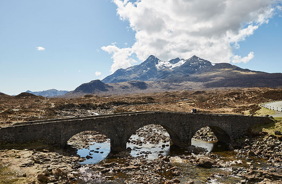 two people walk over bridge on Isle of Sky with mountain in background