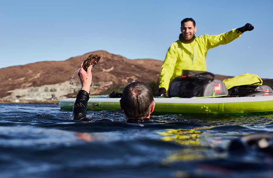 A man comes up from free diving with scallop in hand while his friend celebrates