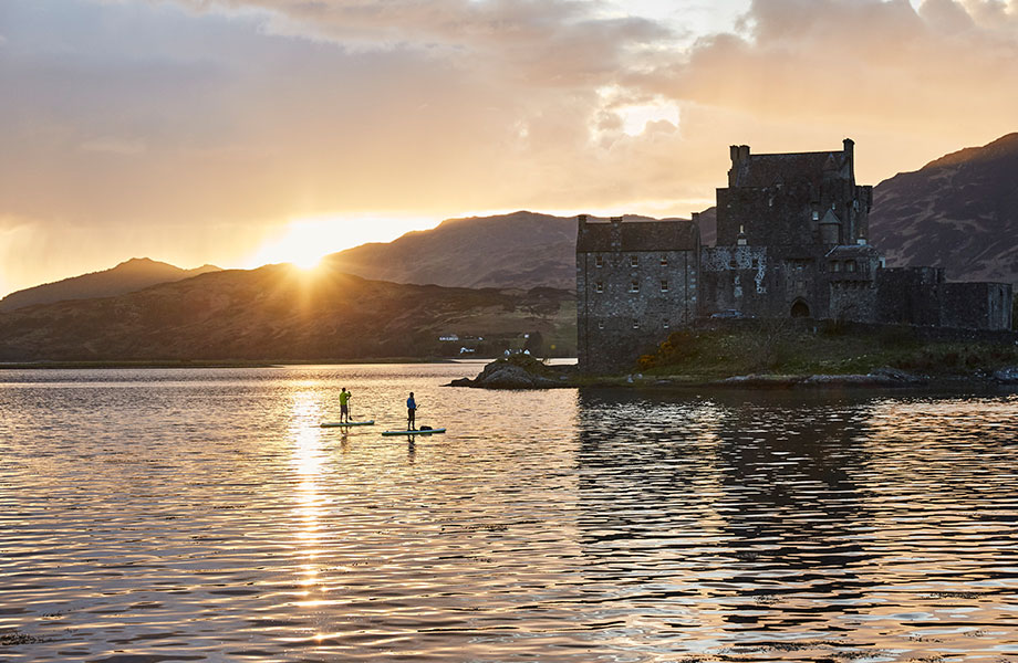 Two paddle boarders look at Castle as sun goes down behind the hills.