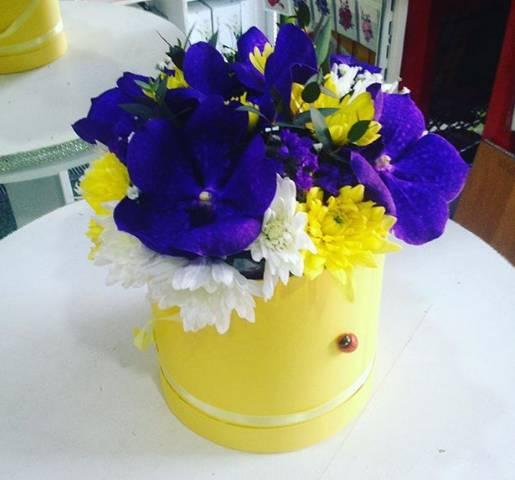 Ljubičaste orhideje i žuto cveće u žutoj kutiji.