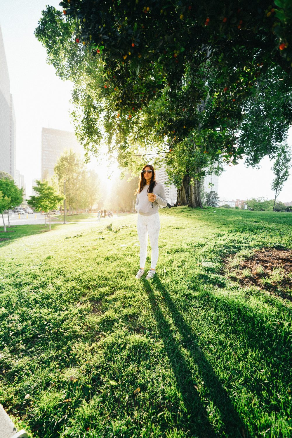 Woman standing in grass with sunshine