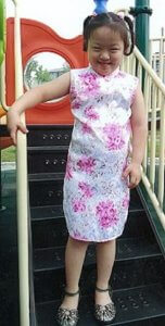 PD: Andrea stands on some playground equipment stairs, holding the railing in a white cheongsam (traditional dress) covered in pink flowers & a repeating floral pattern, along w/ sandals. She has short hair in 2 high pigtails & a huge grin!