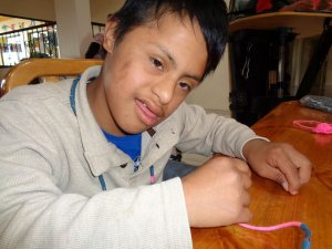 PD: Ansel sits at a table wearing a tan shirt. He looks at the camera w/ a calm expression.