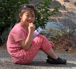 PD: Nora sits on the ground in front of some plants, wearing a pink top & pink polka dot capris. Her hair is pulled back w/ some wispy pieces in front. She is smiling & making eye contact w/ the camera, holding a book in her lap w/ her other hand up near her chin.