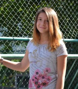 PD: Vanessa has light brown hair & brown eyes. She stands in front of a fence, wearing a gray top w/ writing & pink flowers on it.