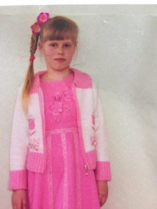 PD: Adelaide wears a pink dress, white sweater, & has 2 pink flowers in her long, braided blonde hair w/ heavy bangs/fringe.