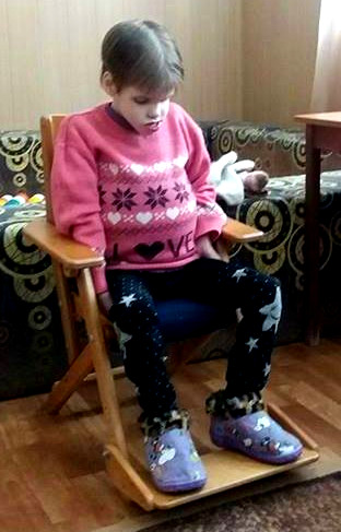 PD: Scout sits in a chair w/ her head tilted down. She wears a pink sweater, black pants, & slippers on her feet.