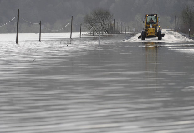 Oregon Department of Transportation vehicles work on clearing the highway of debris near a flooded area of Highway 42 South on Monday afternoon.