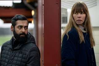 Photo from Greyzone showing Iyad (Ardalan Esmaili) on Left, a wall between and Victoria (Birgitte Hjort Sôrensen) on Right. Both are turned slightly towards each other.