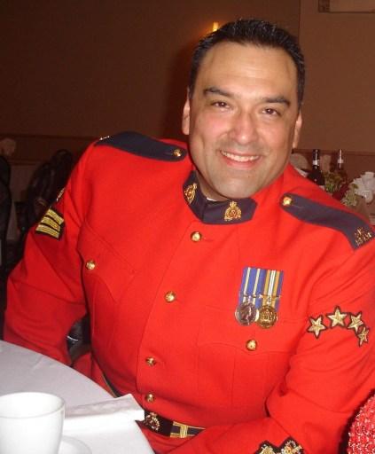 Dan Bradford at table with full dress RCMP uniform.