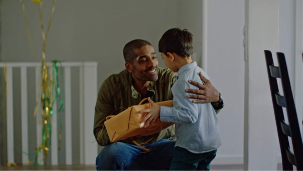 Image shows Alexander Karim as Frank Nordling giving a gift to a small boy in The Lawyer