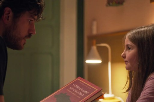 Image shows a scene from Invisible City with Eric holding a Brazilian folklore book looking at his daughter