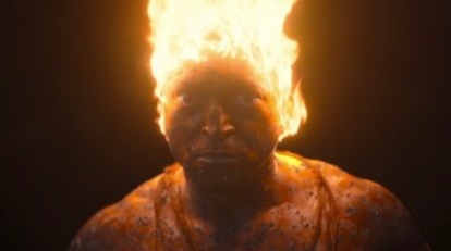 Image shows a figure with his head on fire in a scene from Invisible City