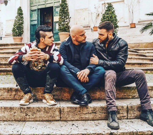 Scene from Suburra: Blood on Rome with Aureliano (right) sitting closely while holding the arm of Cinaglia (centre) whilst looking into his eyes. Spadino (left) sits closely and watches with a sandwich in his hands. They are sitting on steps.