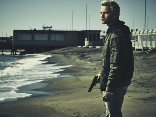 Alessandro Borghi as Aureliano Adami on the beach, holding a gun in a scene from season 1 of Suburra: Blood on Rome