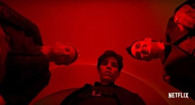 Bright red lit scene from episode 1 of Suburra: Blood on Rome with the three main characters looking down