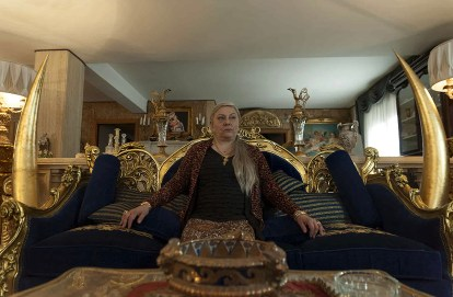 Interior shot of the Anacleti's family home. Gold and black dominate. Adelaide Anacleti (Paola Sotgui) sits on a sofa with gigantic golden tusks either side.