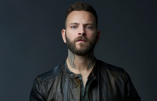 Aureliano (Alessandro Borghi) by season 2 has a complete change of appearance. Dark hair cropped at the sides, beard and neck tattoos of angels' wings.