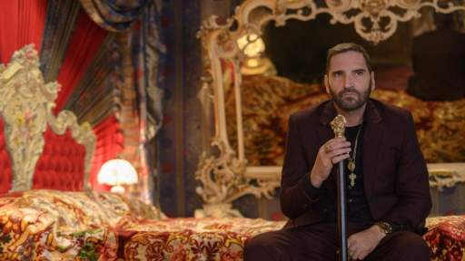 Manfredi Anacleti (Adamo Dionisi) holds a golden topped walking stick while sitting on a bed in a scene from Suburra: Blood on Rome. The bed and room are decorated in red and lots of gold.