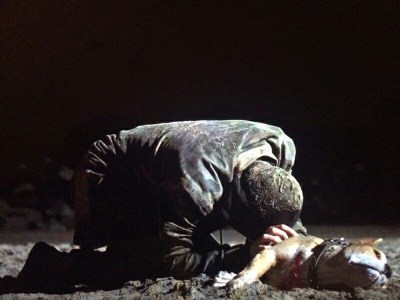 Image of Aureliano Adami (Alessandro Borghi) on his knees on the sand leaning on his dead dog.