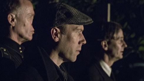 Jakob Cedergren (foreground) as N.B. Lund Ferdinansen, Morten Holst (rear left) as Group Leader and Lars Brygmann as Pastor Kjeldgaard in a scene from Across the Waters