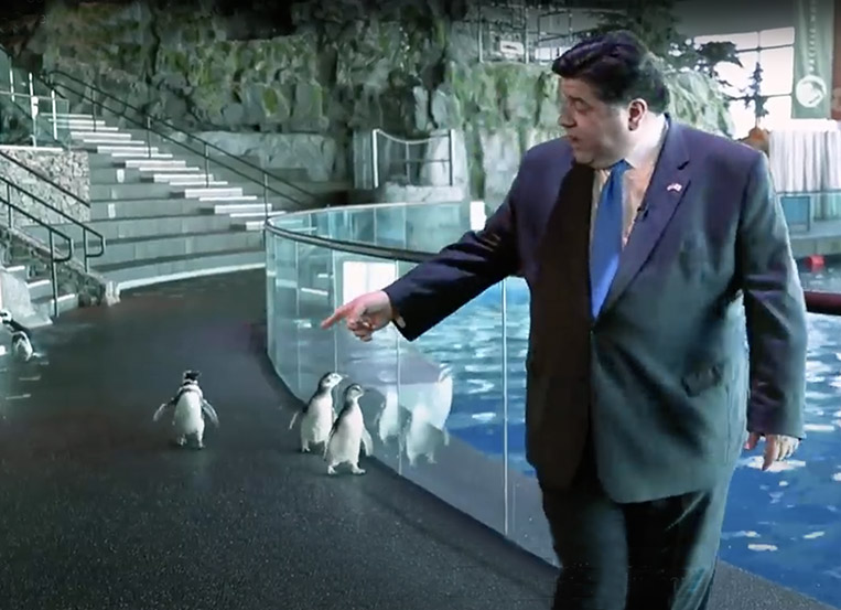 Pritzker and Wellington the Penguin in 'All In Illinois' PSA