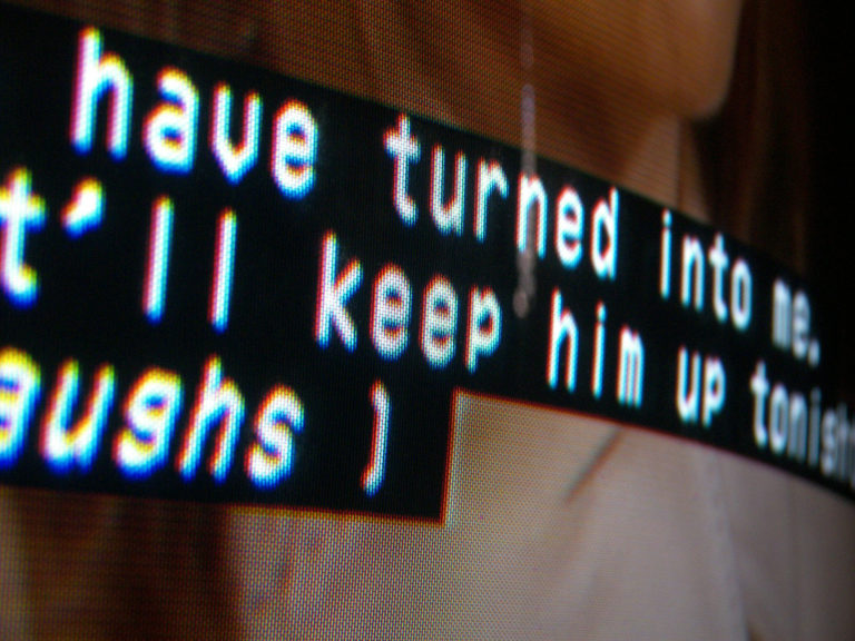 A cropped closeup colour photo of closed captions on a screen, the text being cut off to prevent understanding a sentence.