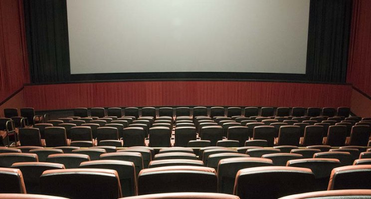Colour photo of a cinema from the back row looking at a blank screen.