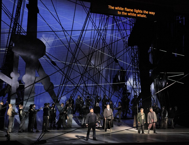 Scene from a modern-set opera with surtitles projected above the stage