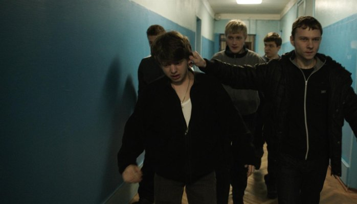 Four boys lead a smaller one by the ear down a dimly lit institutional hallway; a still from the movie The Tribe.