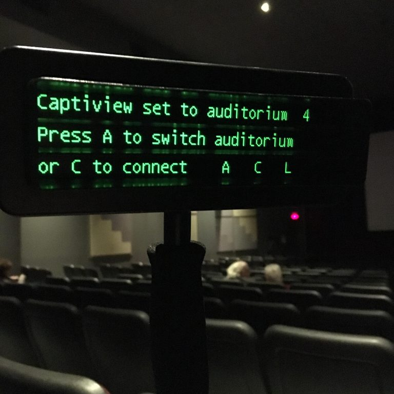 A CaptiView device in the foreground of a dim cinema auditorium; the green digital print gives connection instructions for that cinema.