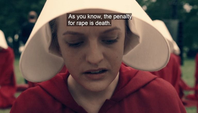Offred looking down, distressed. Caption: As you know, the penalty for rape is death.
