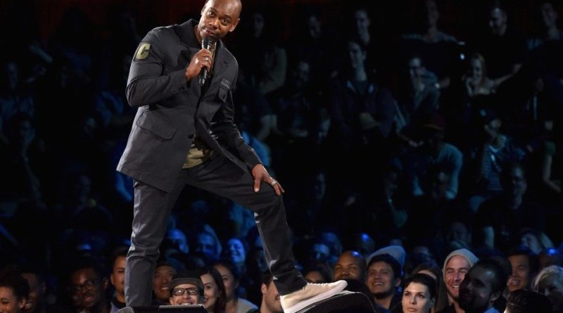 "A wide shot of comedian Dave Chappelle leaning on a speaker during a performance of his stand up routine ""The Age of Spin"" from his 2017 Netflix comedy special series."