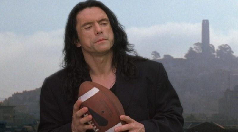 Tommy Wiseau holding a football in a scene from the 2003 film, The Room.