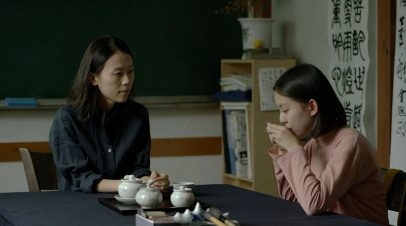 A teacher (Kim Saebyuk) and a teenage girl (Park Jihu) drink tea together in a classroom. Source: Hollywood Reporter