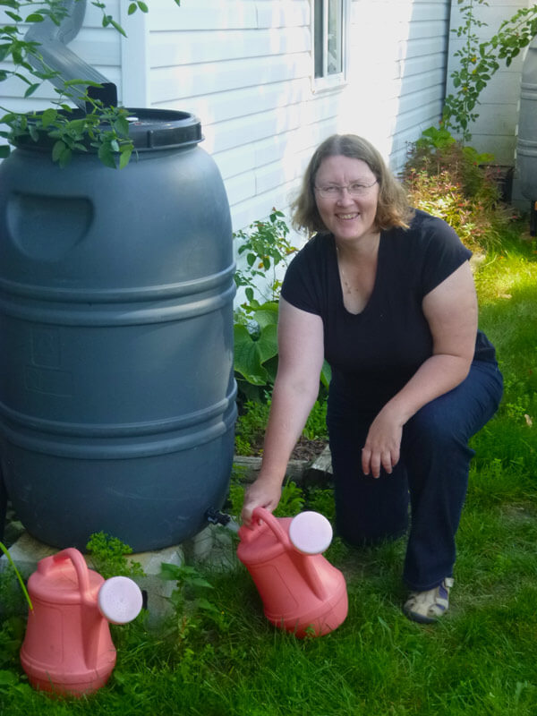 Natalia fills her watering cans up with water collected from her roof.