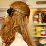 woman looking in open fridge