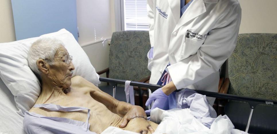 Chirurgien plastique, le Dr Anthony Echo examine la main de son patient, Frank Reyes, avant de procéder à l'opération. ©Pat Sullivan/AP/SIPA