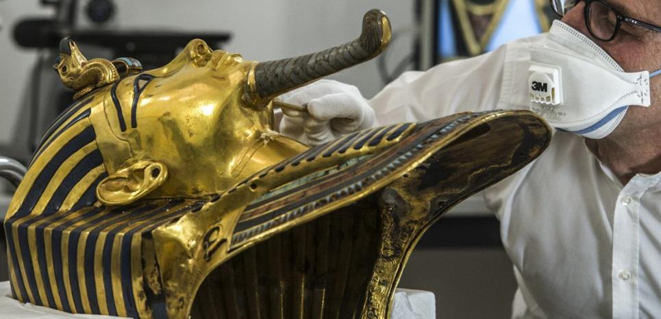 Des chercheurs allemands spécialistes de la restauration travaillent sur le masque d'or de Toutankhamon au musée du Caire en Egypte, le 20 octobre 2015. ©AFP