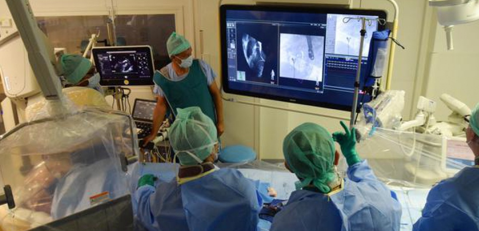 A droite de l'écran l'image échographique montre les structures intracardiaques, à gauche l'image de radioscopie montre la prothèse, au milieu le système Echonavigator permet de fusionner les images échographiques et la radioscopie afin de vérifier le bon positionnement de la prothèse par rapport aux structures intracardiaques ©CHU Toulouse