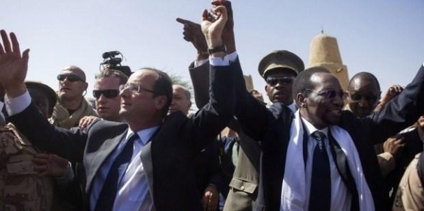 """François Hollande et le président malien par intérim Dioncounda Traoré acclamés par la population, lors de l'arrivée du dirigeant français à l'aéroport de Tombouctou, le 2 février 2013. François Hollande a dénoncé la """"barbarie"""" des islamistes armés qui ont multiplié les exactions dans la ville tout juste libérée. Sa visite au Mali devait se poursuivre dans la journée à Bamako, la capitale du pays. (AFP PHOTO / POOL / FRED DUFOUR)"""